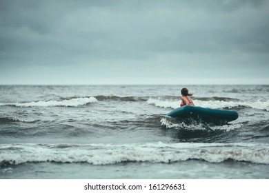 Girl travelling on air mattress in storm