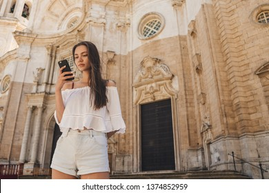 The girl travels alone, looks at the route in the phone against the background of the old cathedral in Europe, Catedral de Santa Cruz de Cdiz