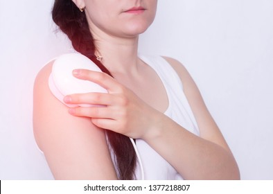The girl treats a sore shoulder joint with the help of physiotherapy magnet, pain relief and inflammation, neck and chest