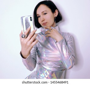 girl in trendy holographic space suit looks smiling into the phone that she is holding. fashion photography