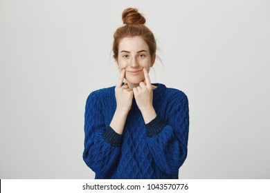 Girl tries to pretend she is happy in front of people. Indoor shot of calm and normal redhead woman in winter sweater pulling smile with index fingers, standing against gray background