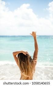 Girl at tropical beach hang loose shaka hand