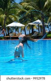 Girl in tropical pool beside the sea