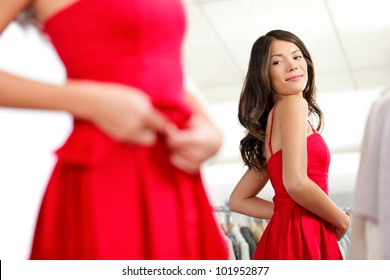 Girl trying dress in looking in mirror cheerful and happy. Cute beautiful mixed race Asian / Caucasian young woman in red dress.