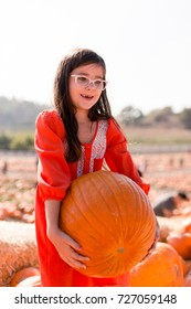A girl is trying to pick up a heavy pumpkin at a pumpkin patch.