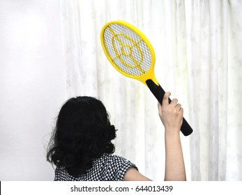 Girl trying to swat mosquitoes with an electronic mosquito racket.