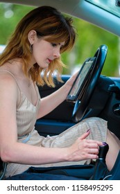 girl trying to understand with a book how to drive a car