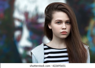 The girl in a t-shirt with long nut-brown hair look in camera. The graffiti in the background.