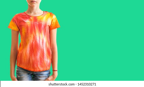 Girl in a t-shirt in the style of tie dye on a green background. White clothes painted by hand.