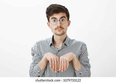 Girl turned boyfriend into puppy. Portrait of cute funny caucasian man with moustache in glasses, holding hands near chest like animal paws and staring with carefree dumb expression at camera