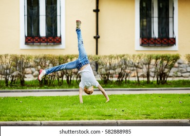 Girl turns cartwheel on grassy lawn in front of house.