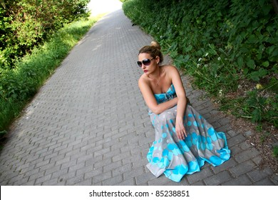 Girl in a turquoise dress sitting on his haunches