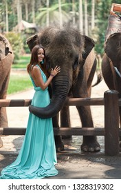 a girl in a turquoise dress and a smile on her face touches a big elephant.