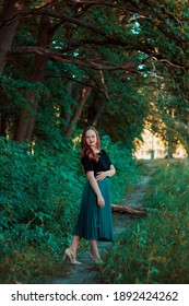 Girl in a turquoise skirt in a fairy forest. Smiling cute girl with red lipstick. Girl on the background of large tree branches