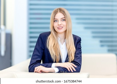Girl TV presenter sitting at a table in a TV Studio preparing to broadcast news live