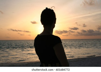 Girl in the twilight watching the sunset over the ocean