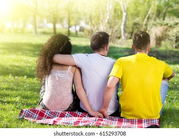 Girl with two boys, one hugging her and another one holding her hand behind his back. Love triangle in park