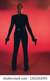 Girl with two guns dressed in black. Standing against red background.