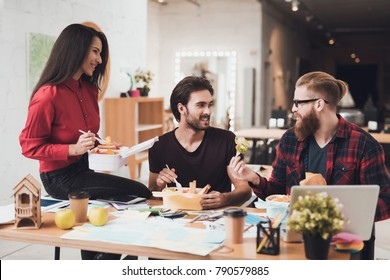 A girl and two guys have a snack at the office. They have a short break. They rest from working together.