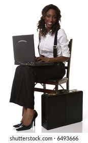 girl typing on computer in chair