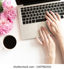 Girl typing on laptop. Home office desk with bouquet of pink peonies, mug of coffee on a white background