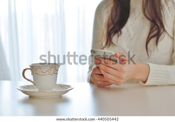 Girl typing on the smart phone at home