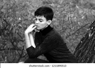 Girl with ultra short hair cut Pixie thoughtfully sad in a knitted sweater in nature black and white photography