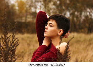 Girl with ultra short hairy pixie on nature on the field among dried flowers in autumn in a red knitted sweater