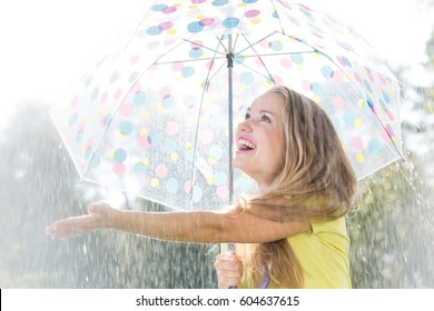 Girl with umbrella catching raindrops during summer day