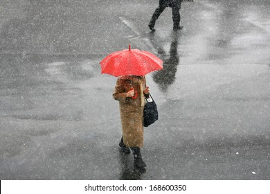 Girl with umbrella during snow storm in the street