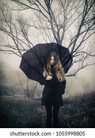 Girl with umbrella in old park. Young woman walking alone in the forest. The image with the effect of double exposure