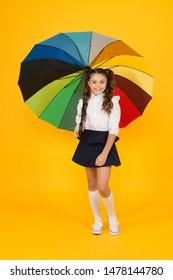 Girl with umbrella. Rainy day walks. Happy childhood. School time. Rainbow style. Colorful life. Schoolgirl happy with umbrella. Fall weather forecast. Fashion accessory. Umbrella protective shield.