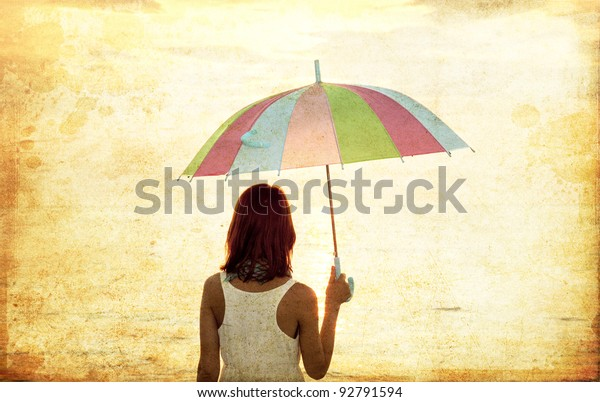Girl with umbrella at sea coast. Photo in old image style.