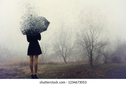 Girl with umbrella standing on the field with trees.