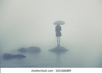 Girl with umbrella standing on a rock in the middle of the water. Alone woman in the fog