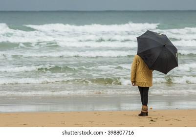 Girl with umbrella walking along the beach shore