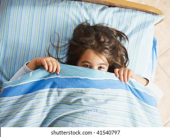 Girl under covers, looking at camera. High angle view