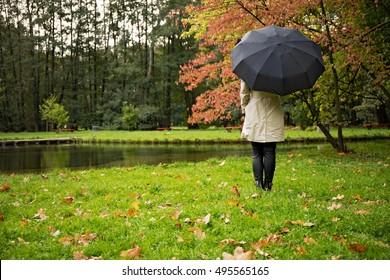 girl under umbrella standing in the rain