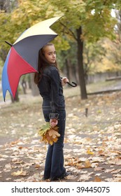 Girl under umbrella and yellow leaves at autumn