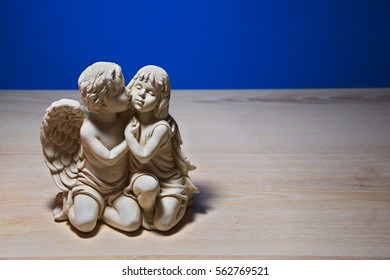 Girl under the wing of an angel, figurine on the table