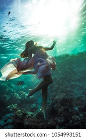 Girl underwater in deep sea, wearing pink long flowing dress, floating over coral reef against bright sun in ripples of water surface