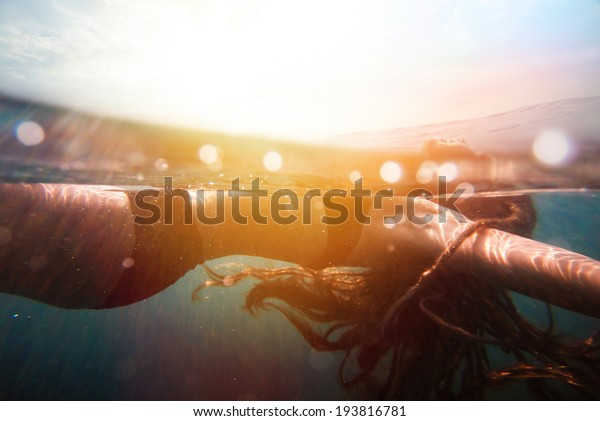 Girl underwater with sun rays. vintage retro style with soft focus, bokeh and sun flare