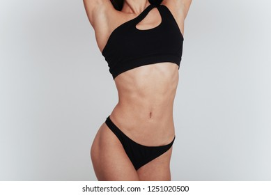 Girl in underwear with slim figure shows her body at the white background.