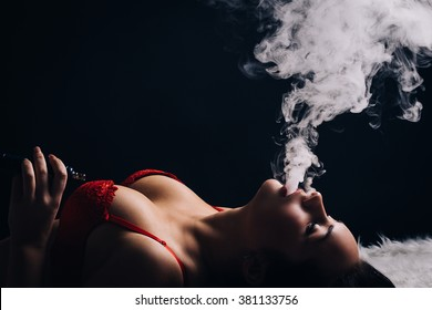 The girl in underwear smoking a hookah lying on the floor