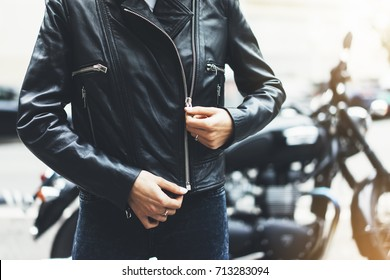 Girl unfastens black leather jacket on background motorcycle in sun flare atmospheric city, hipster biker female hands closeup, motorbike street lifestyle, traveler planing bike route in summer