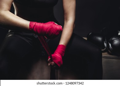 Girl in uniform on black background is preparing for tough fight, wraps his hands sports protective bandages red and pink, lying next to Boxing gloves