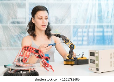 girl in a University laboratory is experimenting with a robot