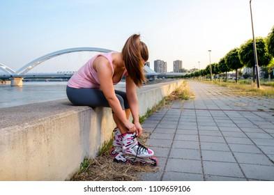 Girl unrecognizable, putting on and adjusting roller skates