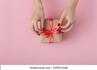 girl unties a ribbon bow on a gift box with hands, female with present wrapped in decorative paper on pink background, top view, concept holiday