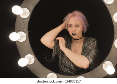 A girl with an unusual make-up, piercings. Shooting in studio.
